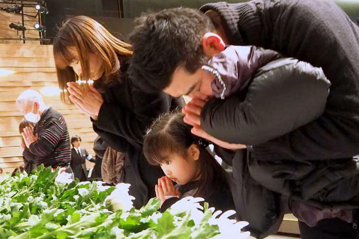 犠牲者を悼み、手を合わせる追悼式参列者