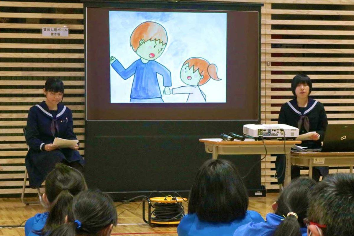 紙芝居をスクリーンに映し、震災時の津波避難の経験を伝える佐野里奈さん(右)と永田杏里さん