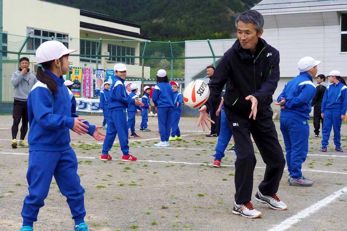 ラグビー教室に参加した三ケ田礼一さん(右)。パス回しなどで児童と交流した