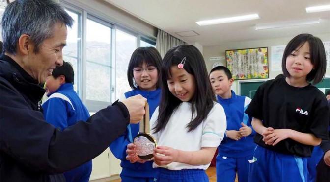 金メダルに触って笑顔を見せる児童