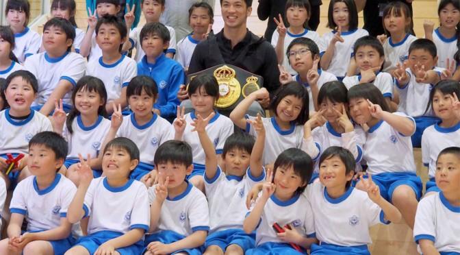 やさしい笑みの村田選手を囲んで「はい、チーズ」。子どもたちは笑顔を広げた