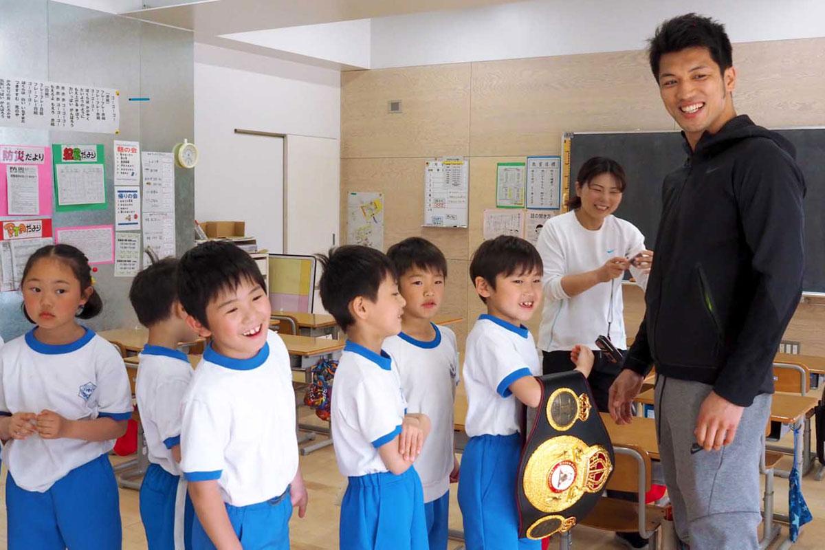 村田選手(右)のチャンピオンベルトを手に笑顔を見せる児童