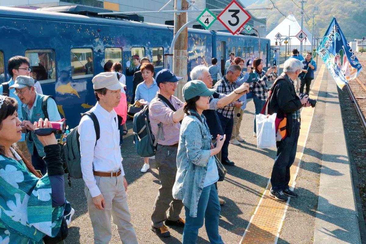 釜石商工高生の虎舞に見入る乗客。郷土芸能のもてなしは運行初日ならでは