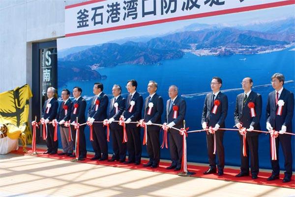国家的プロジェクト釜石港湾口防の復旧を喜びテープカットする関係者