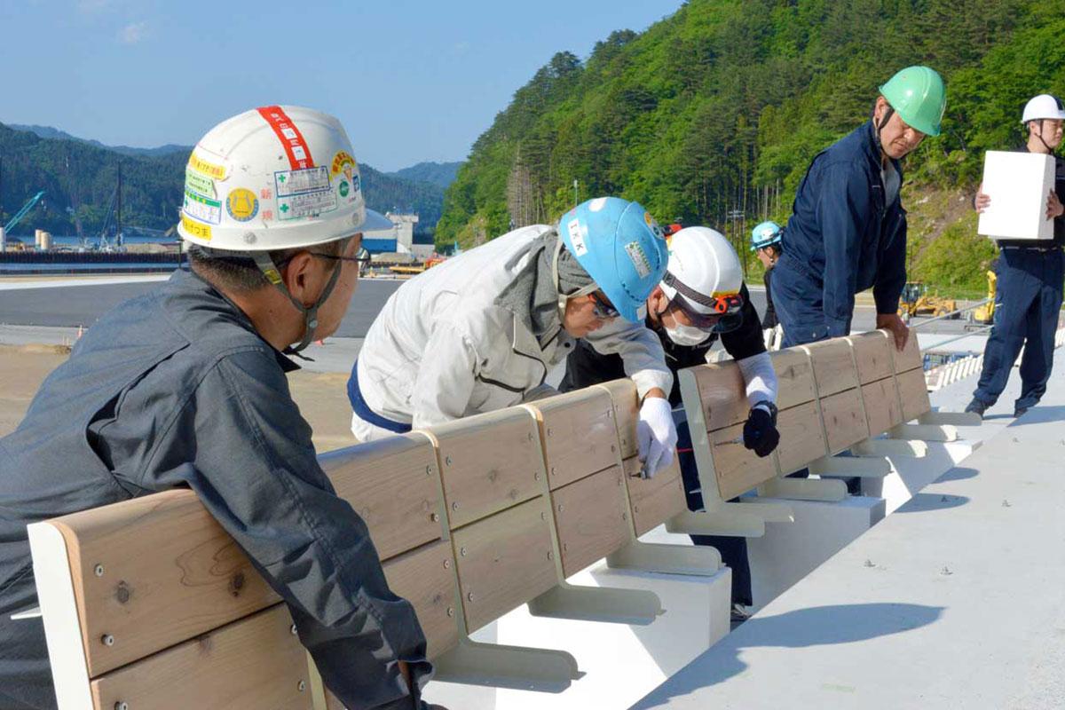 鵜住居町に建設中のスタジアムで進められている木製座席の取り付け作業の様子