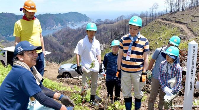 急斜面の植栽地で高橋参事(左)から植樹の方法を聞く参加者