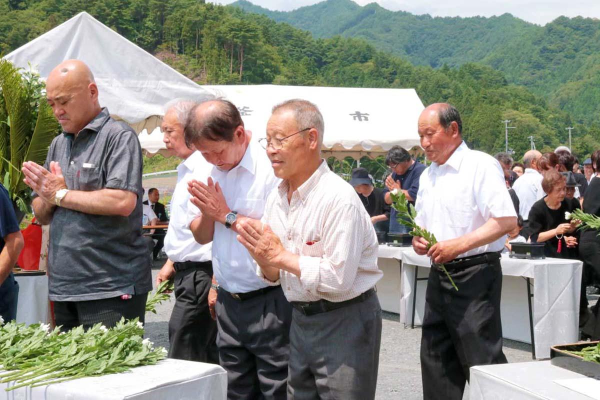 海に向かって献花し、犠牲者を思い祈りをささげる参列者