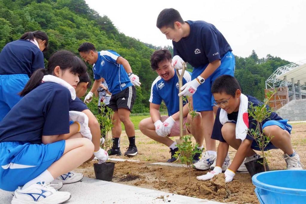完成間近のスタジアム内にある花壇にドウダンツツジを植える釜石東中の1年生と釜石SW選手ら