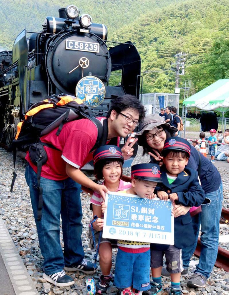 機関車をバックに写真を撮ってもらう家族連れ