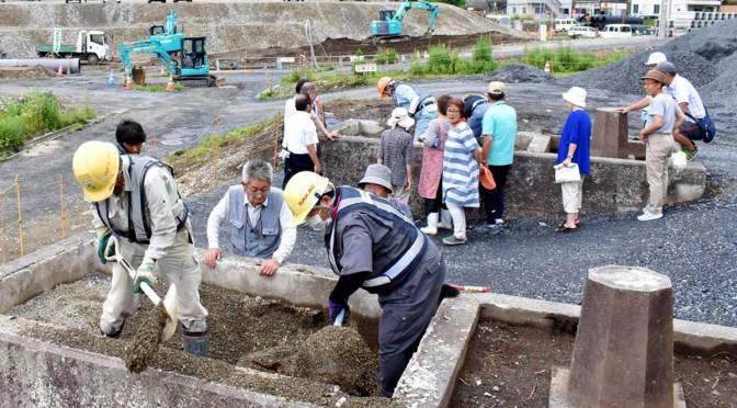 2つの門のふたを除き、表土の砂利を取り除く作業を住民も見守った