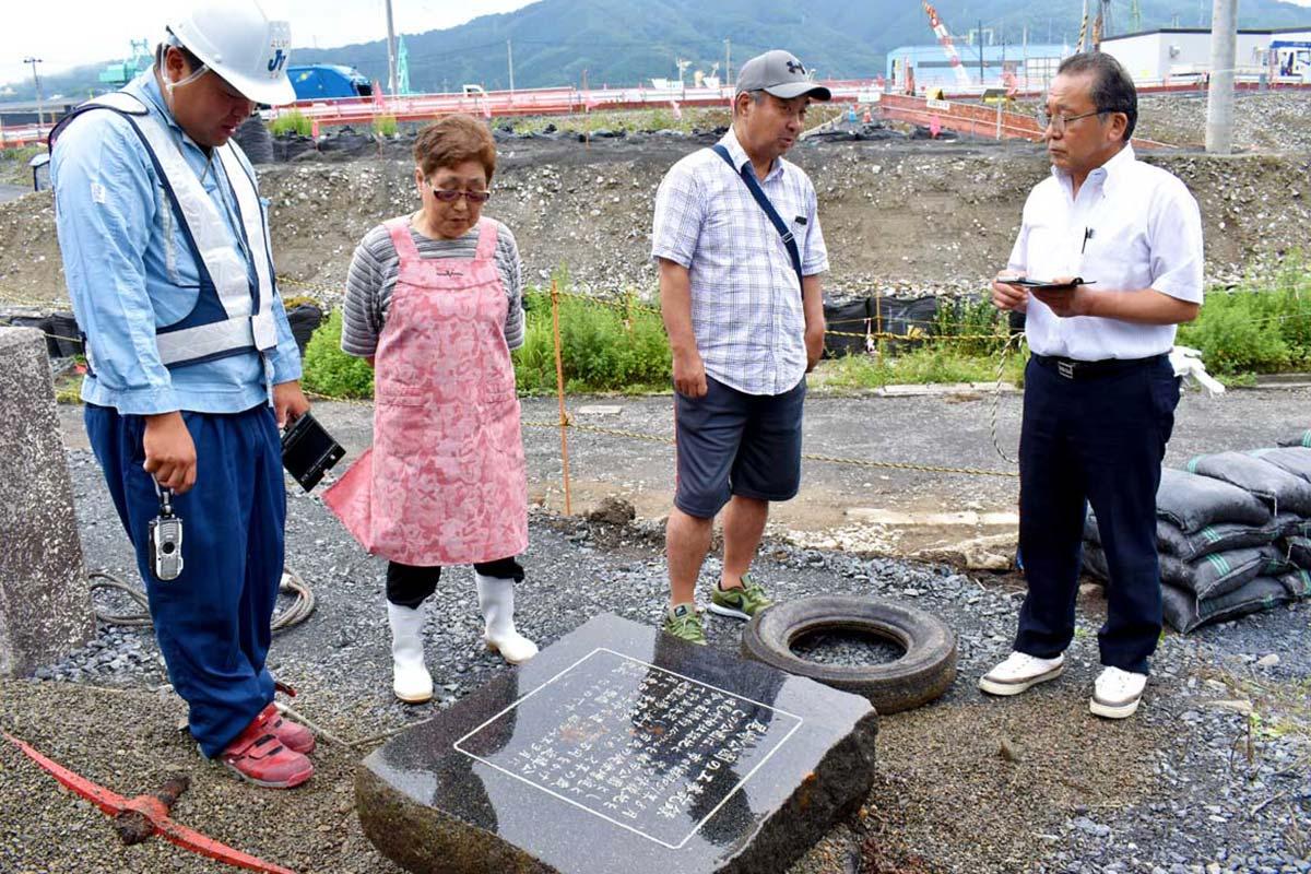 出土した碑を囲み、40年前の一帯のにぎわいを語る住民ら