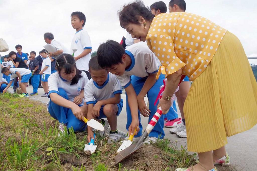 鵜住居小児童と協力してキリの苗木を植える一冊の会会員(右)
