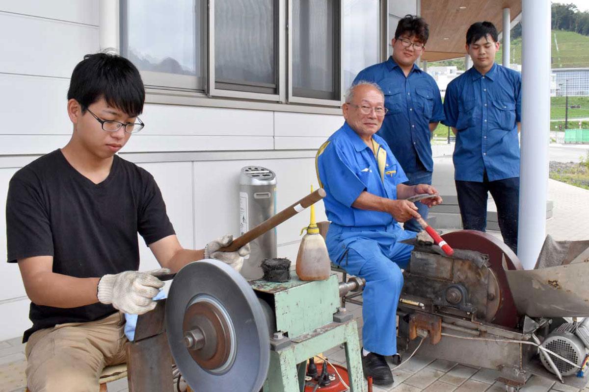 高度な職人技で刃物研ぎの支援を行う堺市の味岡さん(中)と高校生(右後列)