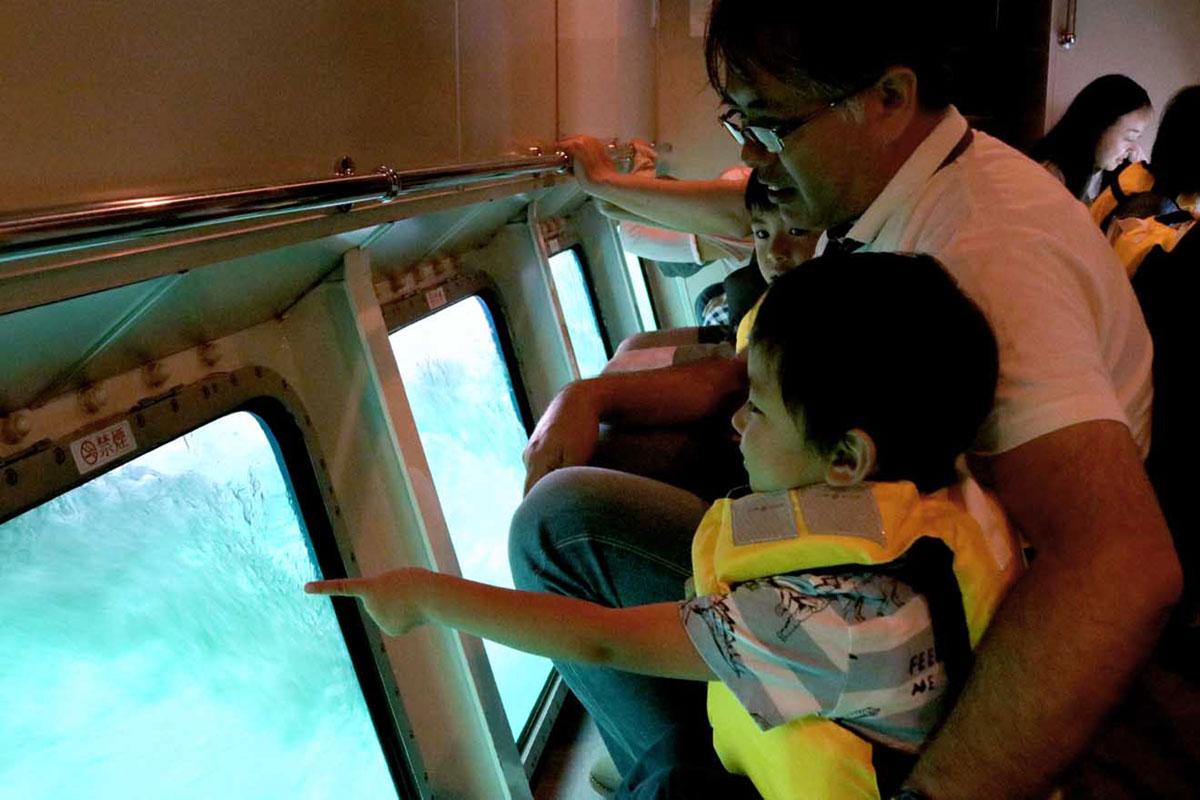 水中観察室で海の中の雰囲気を楽しむ親子