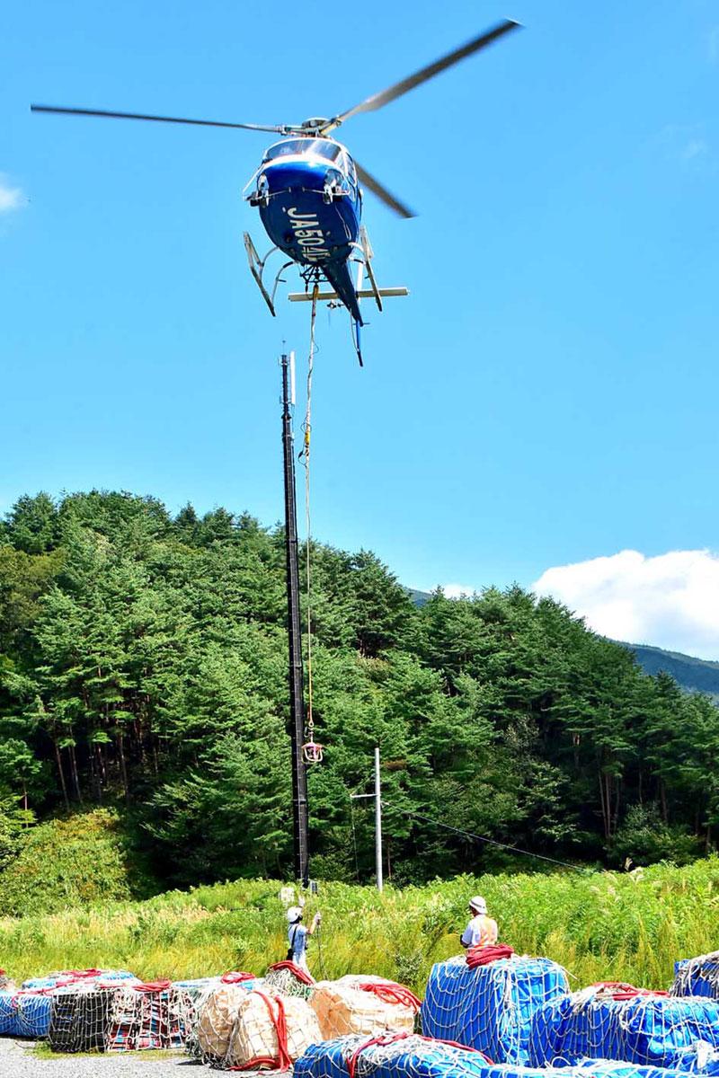 五葉山「石楠花荘」の改築工事に向けて始まったヘリコプターによる資材搬送=6日午前、大船渡市日頃市町の臨時ヘリポート