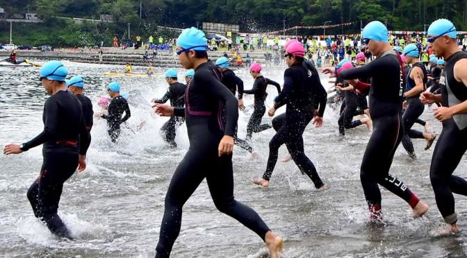 根浜の海に向かって一斉にスタートするトライアスリート=2日午前8時