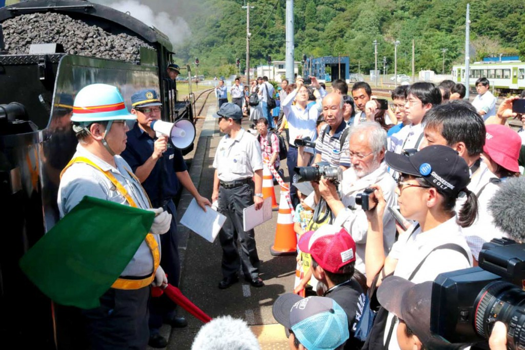 機関車と客車の連結作業の説明に聞き入る来場者