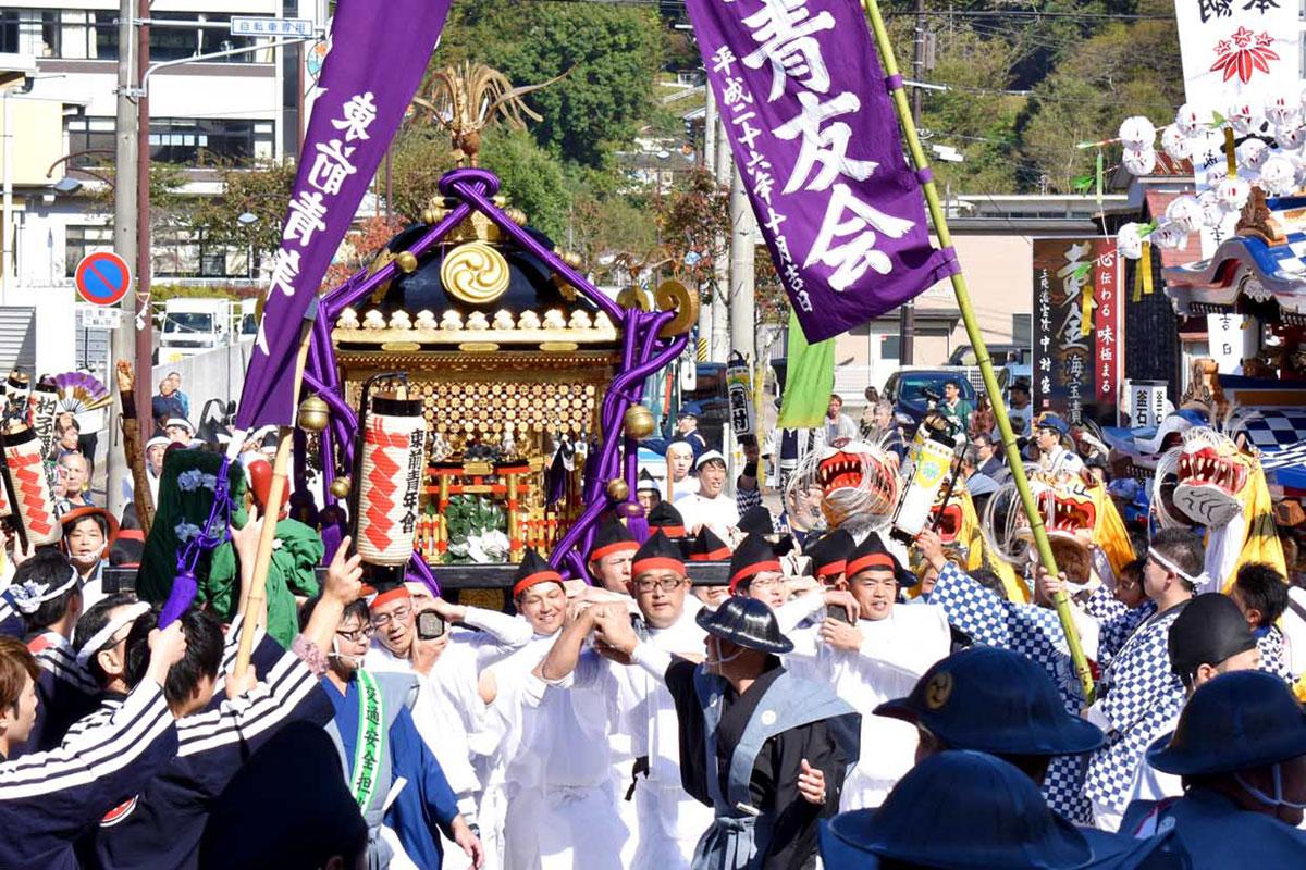 神輿を迎え、郷土芸能が威勢よくはやし立てた=21日午前10時43分、鈴子町の釜石製鉄所正門