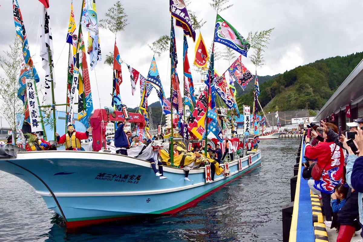釜石魚市場の岸壁から多くの見物客がカメラを向けた「曳き船まつり」