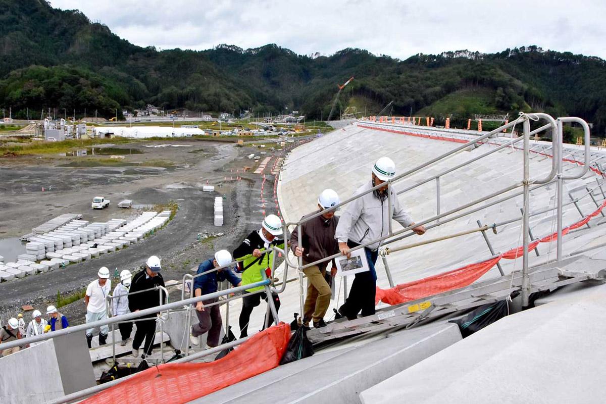 片岸地区を背景に防潮堤の階段を上る地元住民ら