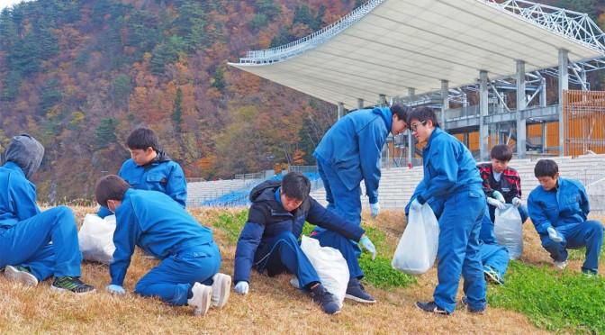 釜石鵜住居復興スタジアムで草取りをする弘前実業高生