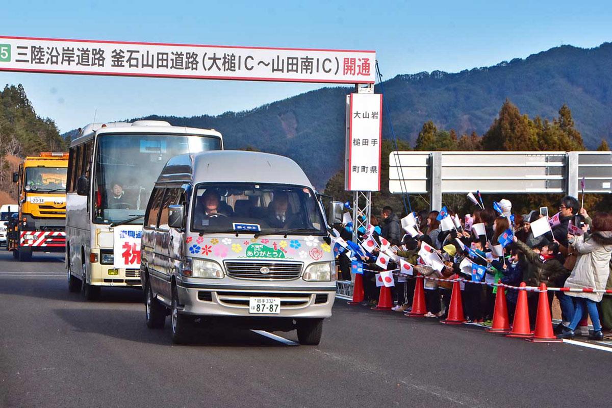 開通の車両パレードを小旗を振って見送る保育園児ら