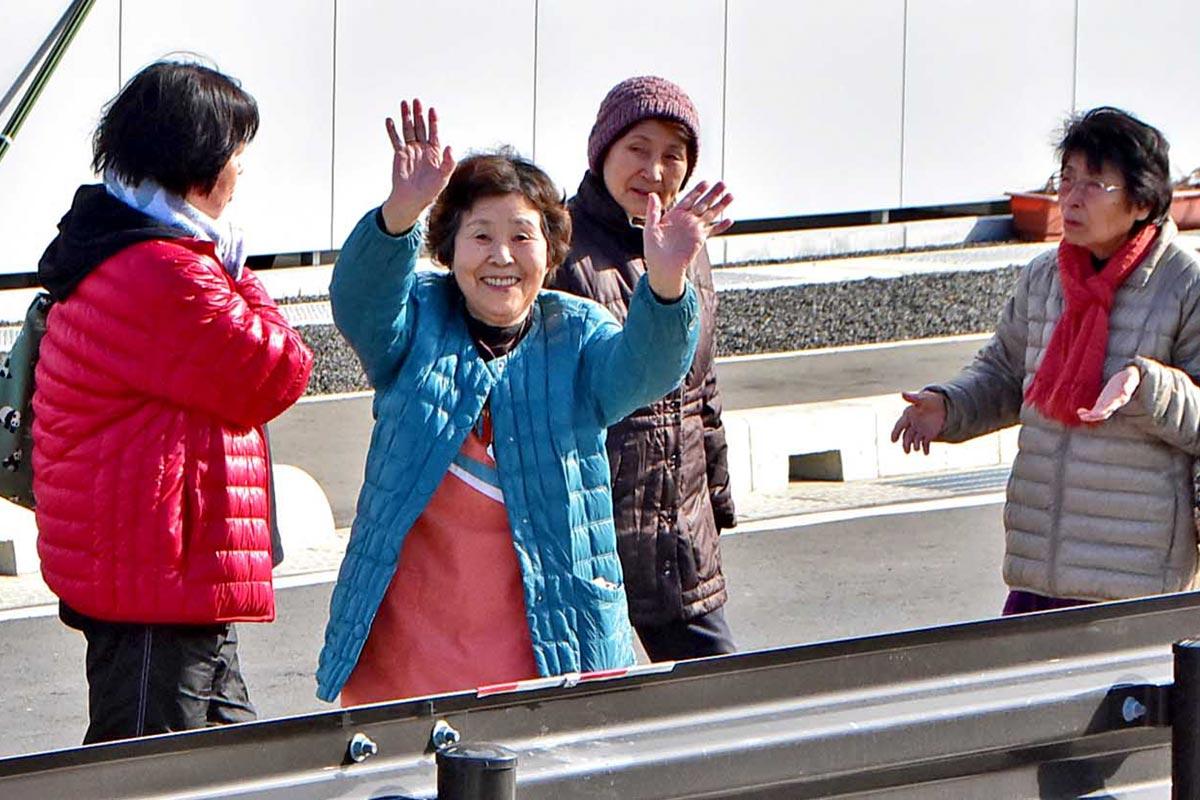 待望の試運転開始に手を振って喜ぶ住民