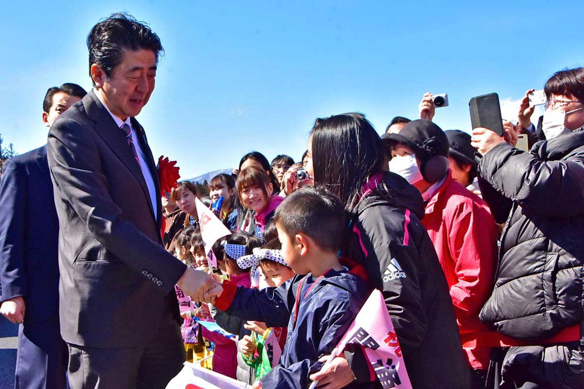 歓迎する子どもらに握手で応える安倍首相