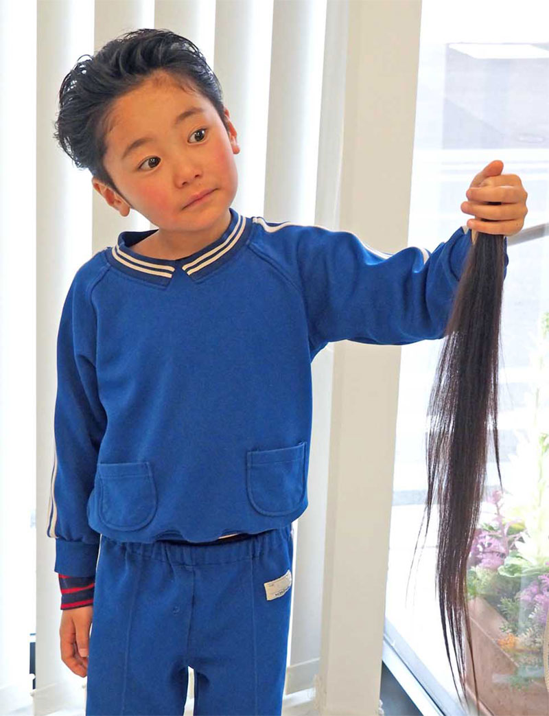 ばっさり切った髪の毛を手にする和田起太朗ちゃん