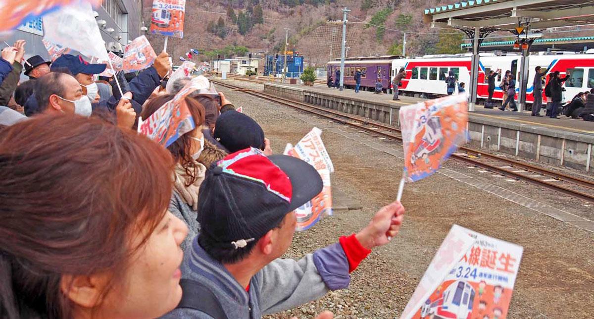 小旗を振り、記念の一番列車を見送る人たち=23日午前11時40分、釜石駅