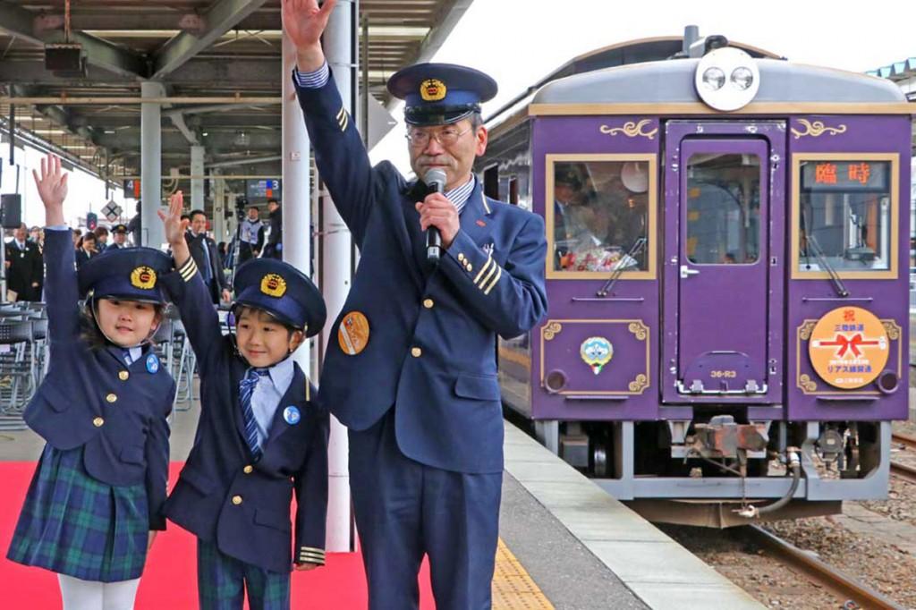 釜石駅長とともに「出発進行」と手を上げる双子の園児