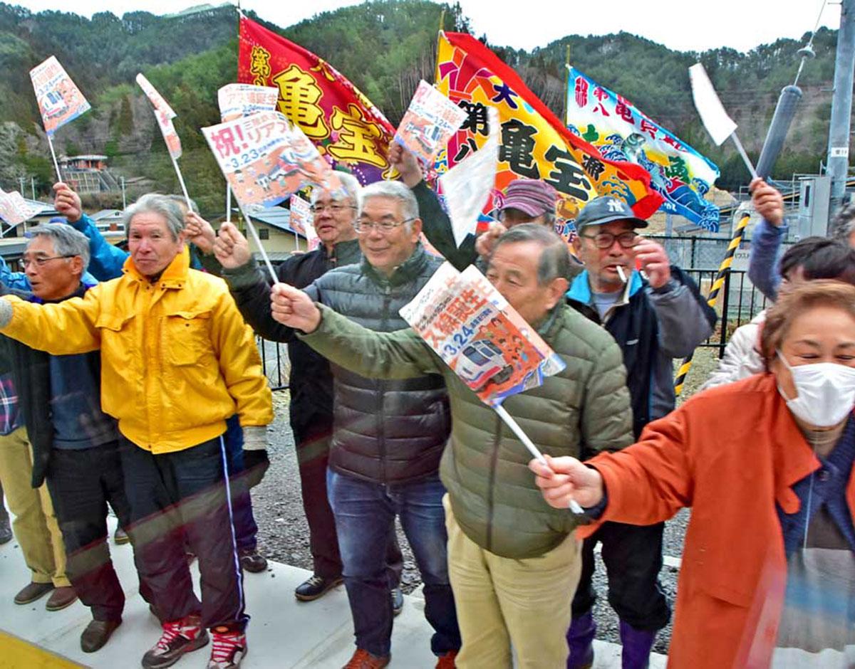 大漁旗や小旗を振り、記念列車を迎える住民=両石駅