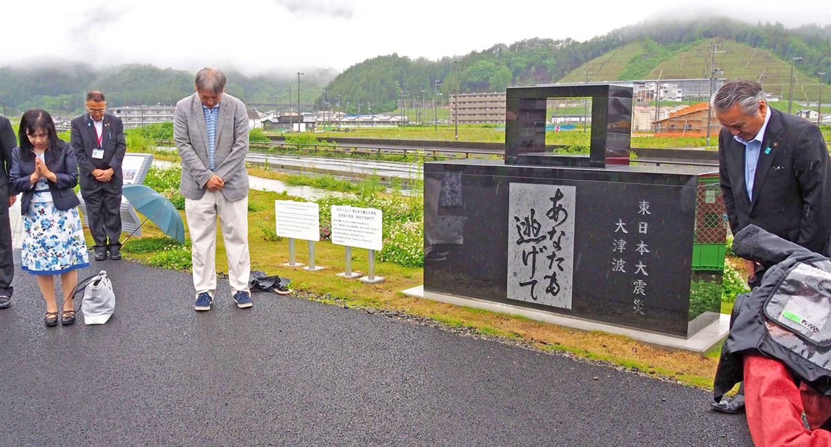 震災祈念碑を除幕し、海に向かって黙とうする関係者