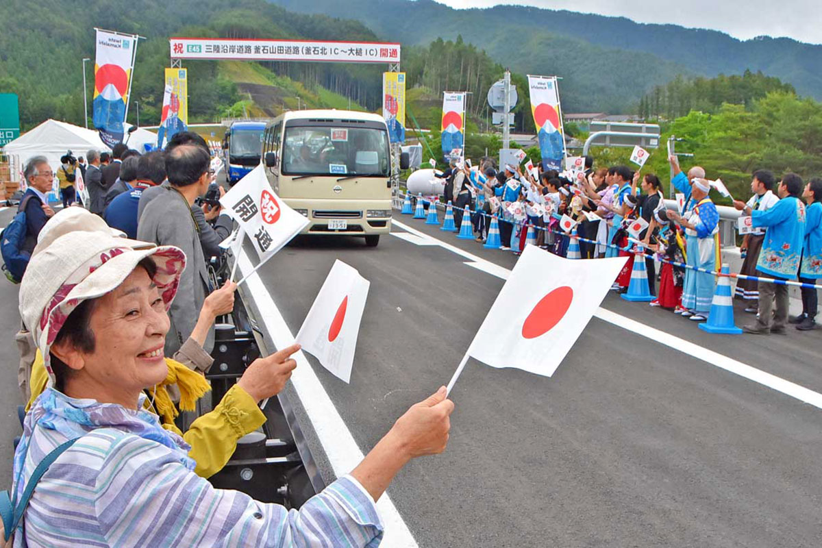 釜石市と大槌町がやっと高速道で結ばれ、小旗を振って喜ぶ地域住民ら=22日、大槌IC付近で