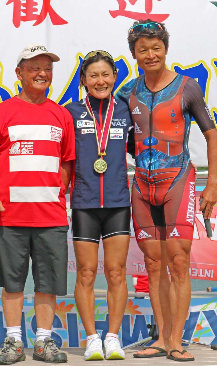 井出樹里さん(中央)のメダル贈呈に立ち会った白戸太朗さん(右)