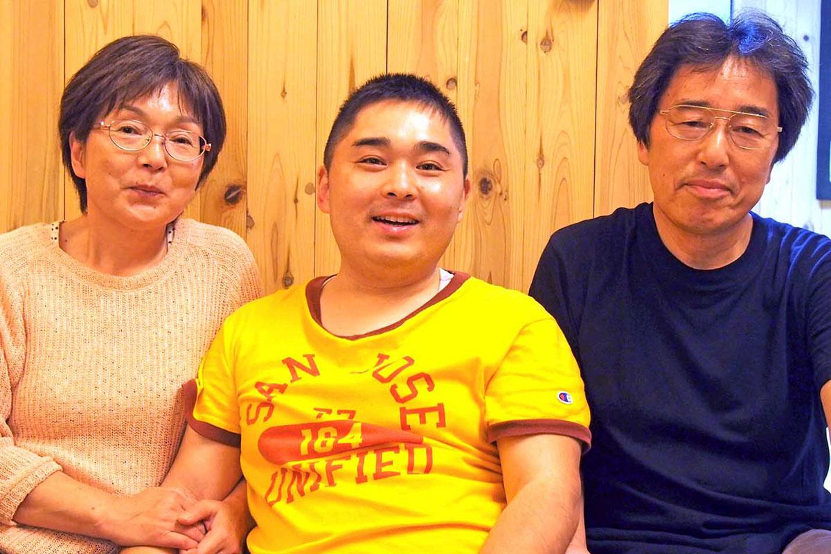 家族に囲まれ笑顔を見せる覚さん(中)