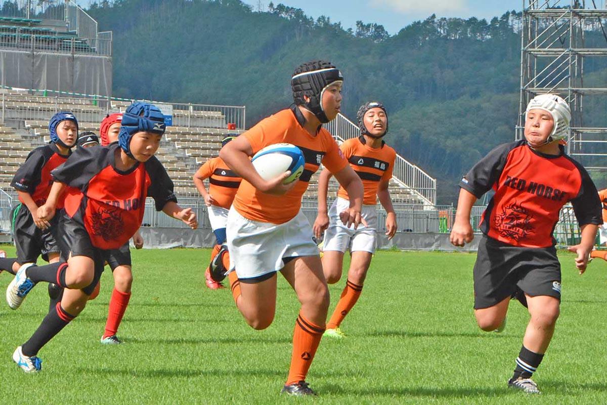 釜石鵜住居復興スタジアムの芝生の上で熱戦を繰り広げる東北のラグビー少年ら