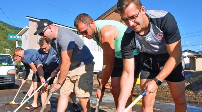 台風豪雨で泥にまみれた千鳥町で、土砂の除去作業に汗を流すカナダ代表チームの選手やコーチら=13日午後