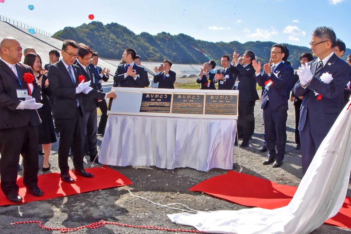 防潮堤の完成を祝い、感謝の銘板を除幕した関係者