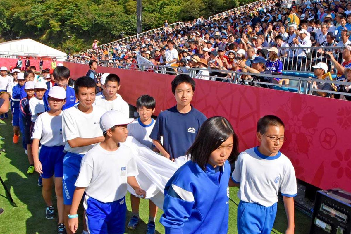 感謝の旗を携え入場する小中学生の代表