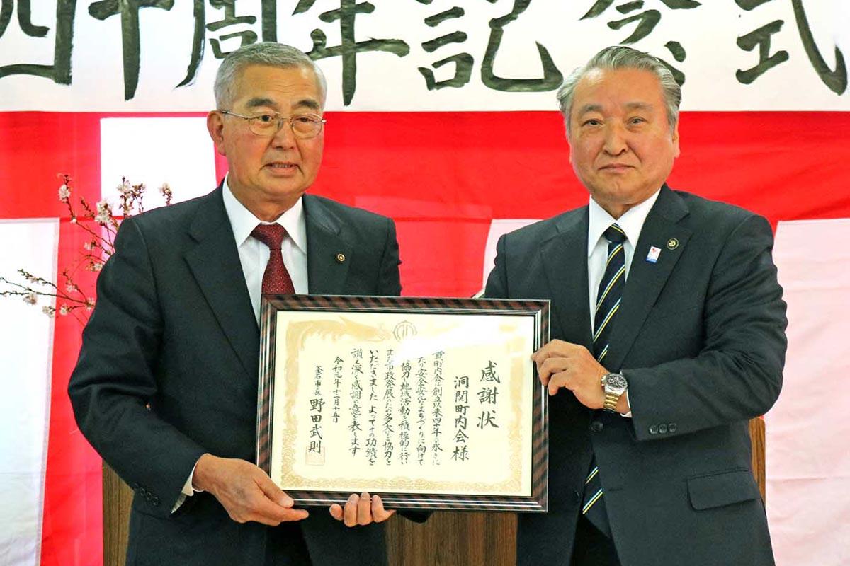 野田武則市長から感謝状を受け取った菊池秀明会長(左)