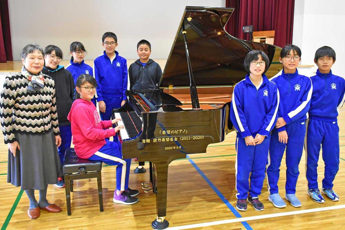 「希望のピアノ」を喜ぶ唐丹小高学年の児童と「唐丹希望基金」の高舘代表(左)