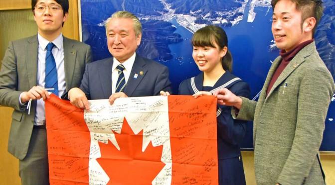 感謝の寄せ書きを手にカナダに留学する菊池莉歩さん(右から2人目)