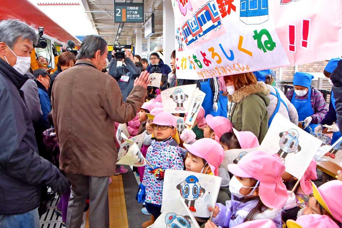 「これからも よろしくね」と手製の横断幕で歓迎する地元の幼稚園・保育園児ら