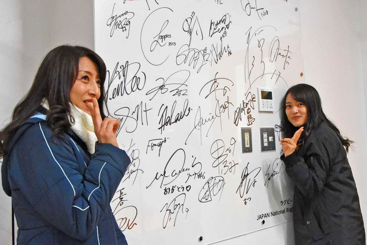 ロッカールームに残された日本代表メンバーのサインをバックに記念撮影