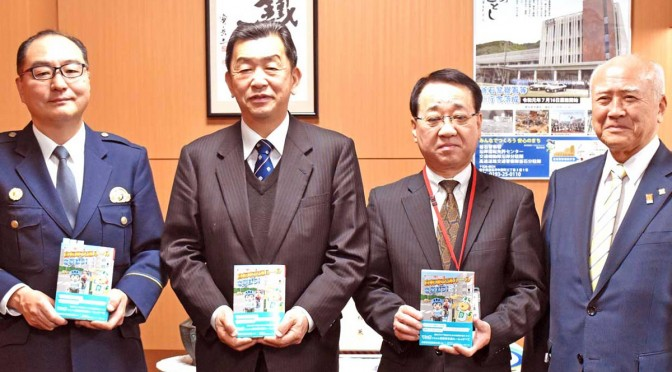 子ども、家庭の交通安全を願いマンガ読本を学校に寄贈した釜石安協の菊地会長(右)