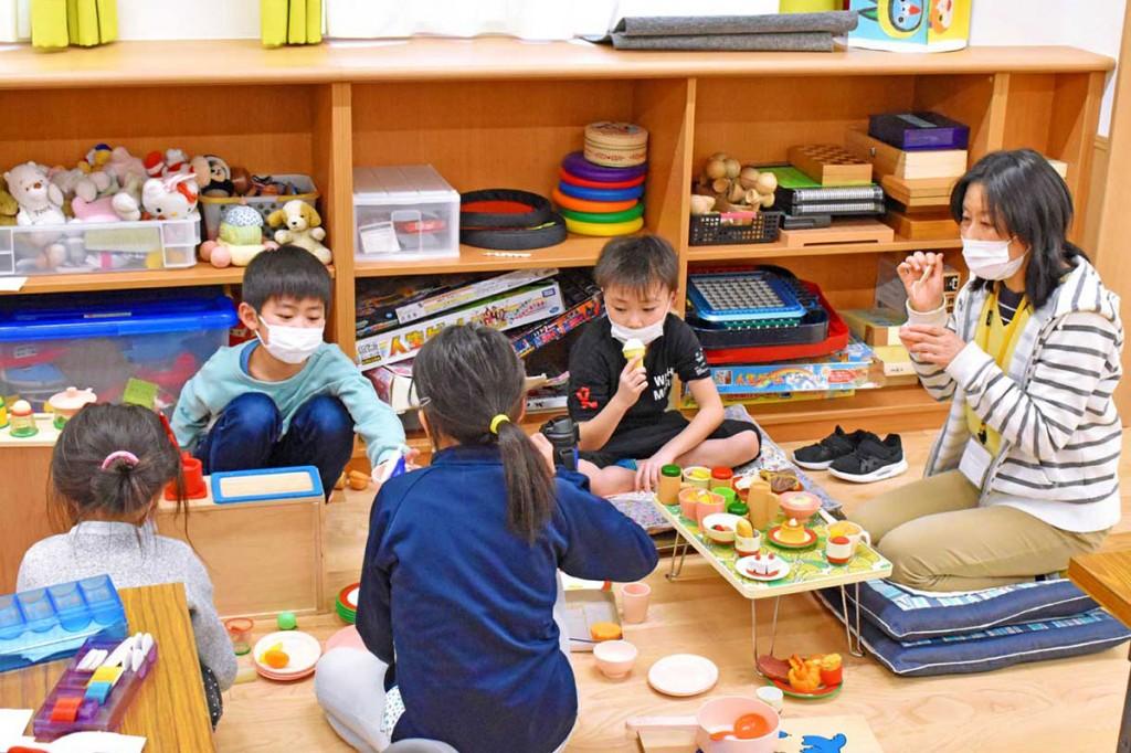 マスクを着けた児童を、学習支援員(右)が細やかな心遣いでサポート=9日午後、上中島児童館
