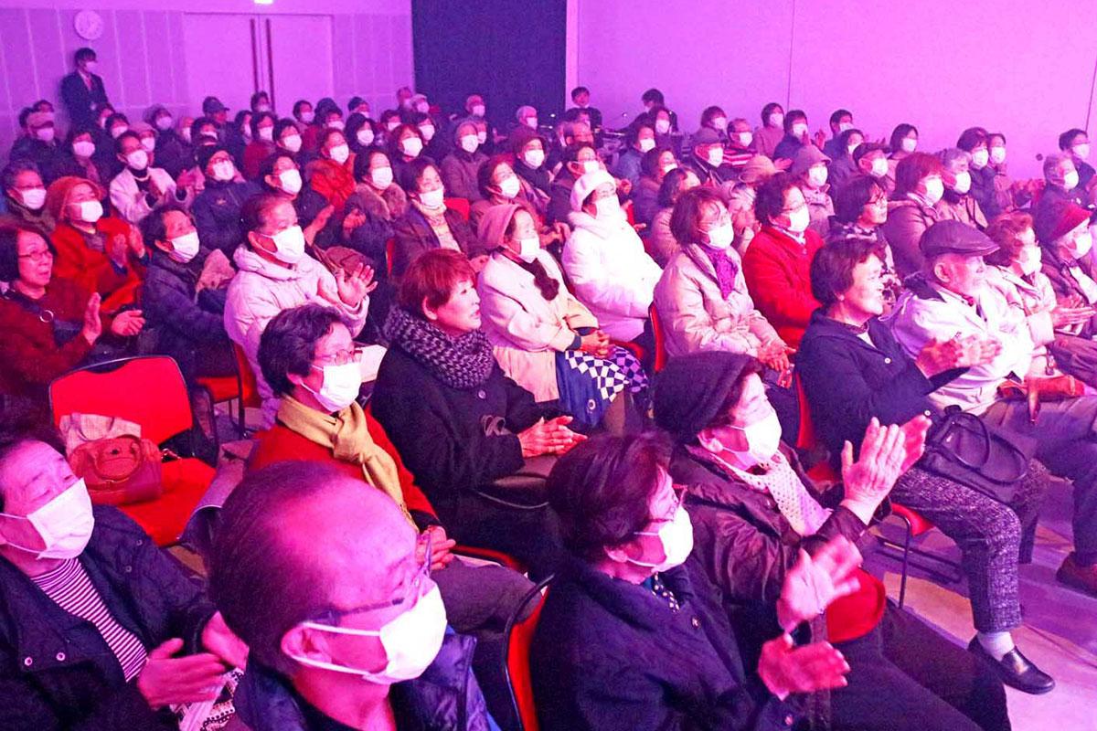 手拍子をしながら、多彩な歌のステージを楽しむ観客