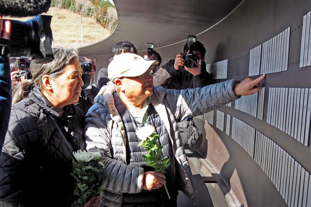 掲示された犠牲になった人の名前に触れる遺族ら