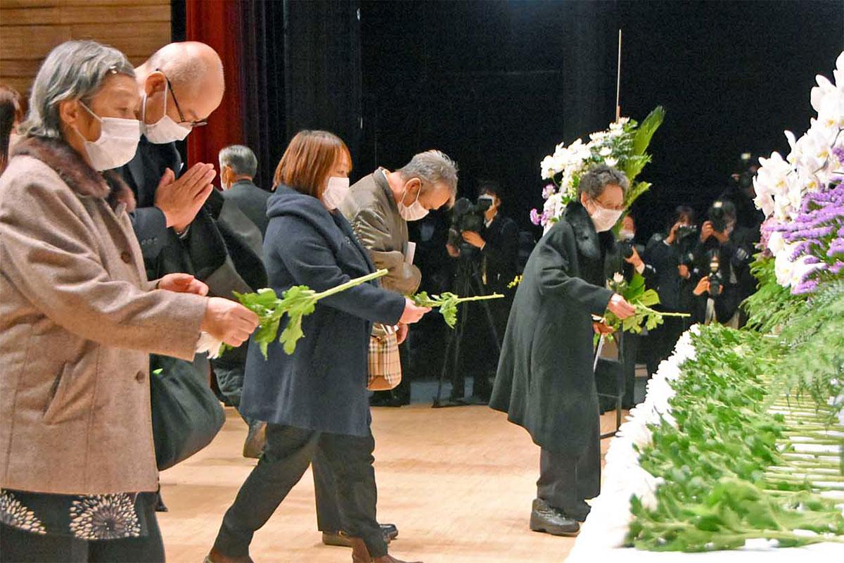 祭壇へ菊の花を手向ける遺族ら